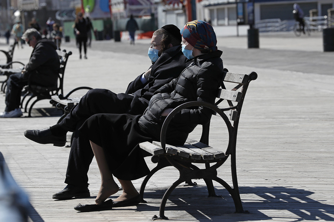 Two people wear face masks as they sit on a bench in the sun at the Coney Island boardwalk in the Brooklyn borough of New York. Credit: Kathy Willens/AP Photo